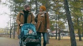 ходить : Two young parents walking their baby in a pram in the park