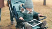 pram : Tilt-up of two parents pushing a stroller with baby and tablet on his knees Stock Footage