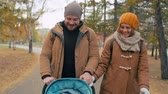 pram : Young parents enjoying their time walking with cute baby in the park Stock Footage