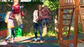 oynamak : Mother and elder sister pushing little boy and girl on swings in backyard playground Stok Video
