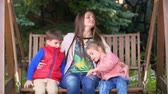 prole : Happy young mother embracing her kids on a swing bench Vídeos
