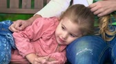 rodzina : Adorable little girl lying on mothers lap and talking to mom