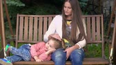 prole : Loving mother stroking a head of her cute little daughter on a swing bench