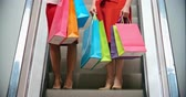escada rolante : Two pretty women with colorful shopping bags going down the escalator