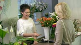 caixa : Female customer paying with credit card for a bouquet in flower shop