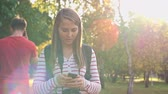 клетка : Young woman walking with camera in the park and texting a message on her smartphone Стоковые видеозаписи