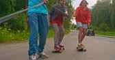 dostihy : Young skaters holding a rope together while riding longboards