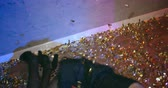 confete : Man taking picture of wasted girl lying down on dance floor in confetti Vídeos