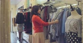shopping : Two beautiful women shopping together in fashion store Stock Footage