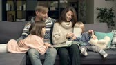 prole : Mom and dad sitting with their adorable children on sofa and watching family photo album