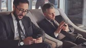 vício : Two business partners checking their social profile on their smartphones