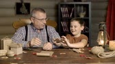 vnuk : Loving grandfather making a wooden elk toy for his grateful grandson