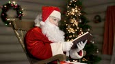 празднование : Santa sitting in wooden armchair near illuminated Christmas tree and reading a book