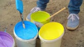 escova : Hand of painter dipping a brush into a bucket with blue paint surrounded by other colors