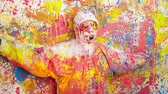 malovat : Person wearing protective coveralls standing by paint-splatter wall and being covered in multi-colored paint