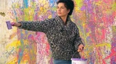 painting : Beautiful female painter splashing colorful paint on walls in slow motion Stock Footage