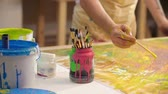 многоцветный : Artist taking a paintbrush, dipping it into yellow paint and making strokes on abstract painting