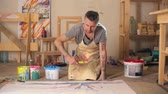 tuval : Artist sitting on floor at his studio and splattering paint on canvas Stok Video