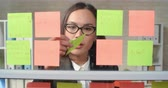 стена : Young businesswoman reading sticky note reminders and removing them from glass wall