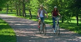 randka : Young couple riding bikes through park on summer day