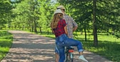 veículo : Man on bike giving a ride to a charming woman in park