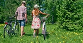 randka : Couple with bicycles walking through dandelion meadow Wideo