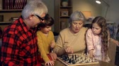 pedaços : Grandparents teaching their little grandchildren how to play chess Vídeos