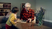vnuk : Senior man teaching his grandchildren to play chess at home