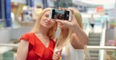 obrázky : Beautiful mother and daughter taking selfie together in shopping mall