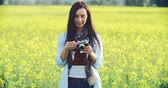 pastime : Pretty lady taking a picture with camera in the meadow and smiling