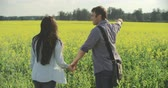 randka : Happy young couple kissing and running through blooming meadow together