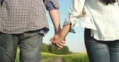 randka : Close-up of couple walking in countryside and holding hands Wideo
