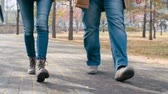 bota : Close up of legs of man and woman walking towards the camera in the park