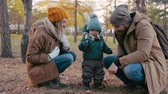 листва : Mom and dad playing in the park with their little son: father showing him how to throw pinecone on the ground Стоковые видеозаписи