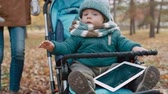 pram : Tilt up of young parents walking in the park with baby sitting in stroller with digital tablet Stock Footage