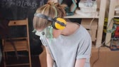 ferramentas : Young woman wearing protective eyewear, ear muffs and gloves while working in carpenter workshop Vídeos