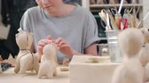 pastime : Tracking shot of young female artistmaking papier-mache dog figures of craft paper Stock Footage