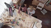papier : Crane viewof two young women sitting at wooden table in handmade studio and making handcrafted papier-mache toys of craft paper