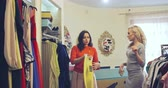 vestuário : Two pretty young ladies shopping together in clothes boutique: one girl holding hanger with yellow pants and showing them to her friend Vídeos