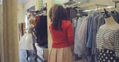 divat : Beautiful blonde girl enjoying shopping with her friend: she trying on tulle skirt, dancing and laughing in fashion boutique Stock mozgókép