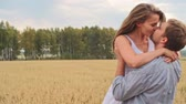 ziarno : Happy woman running to her boyfriend, he spinning her around and kissing in the wheat meadow Wideo