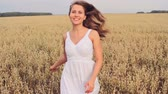 zboże : Pretty young lady in white dress running through golden meadow towards the camera in slow motion