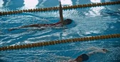 piscina : Sportsman and sportswoman swimming backstroke in the pool
