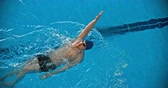 nadador : Directly above view of man in goggles and cap swimming backstroke in the pool