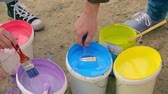 разноцветные : Close-up of house painters dipping paintbrushes into buckets with multi-colored paint Стоковые видеозаписи