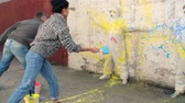 malovat : Street artist splashing paint on outer wall and two people in protective coveralls standing by it, slow motion