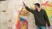 traçado : Artist giving a high five to a girl in protective coveralls after tracing her silhouette on paint splattered wall Vídeos
