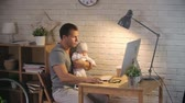 working parents : Handsome father sitting with his baby boy and working on a computer Stock Footage