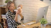 prole : Young mother holding her newborn baby and typing something on a computer