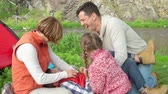 mama : Mother, father and daughter tickling little boy on the lawn Wideo